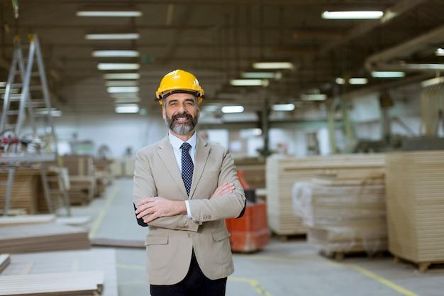 Portret przystojny biznesmen w garniturze z hełmem w magazynie