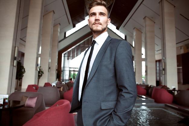 Portret przystojny biznesmen w miejskim otoczeniu.