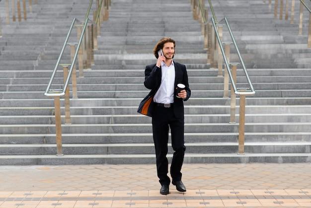 Portret przystojny biznesmen z telefonem, filiżanka kawy na ulicach miasta