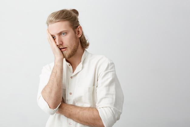 Portret przystojny blond brodaty mężczyzna robi twarz dłoni z zirytowanym lub zmęczonym wyrazem