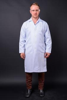 Portret przystojny blondyn lekarz jako naukowiec z okularami ochronnymi na czarnej ścianie