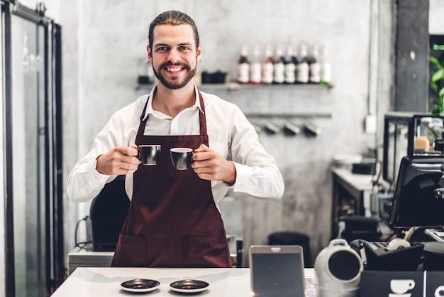 Portret przystojny brodaty barista mężczyzna właściciela małego biznesu uśmiecha się filiżankę kawy i trzyma w kawiarni lub sklep z kawą. męska barista pozycja przy kawiarnią