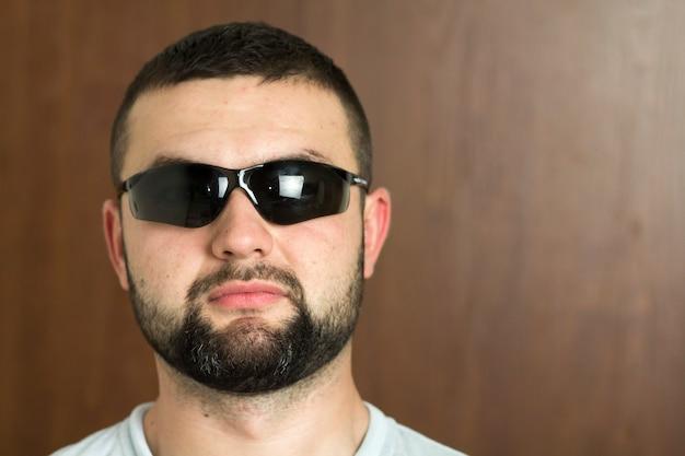 Portret przystojny brodaty czarnowłosy inteligentny nowoczesny młody człowiek w okularach z krótką fryzurą i miłymi czarnymi oczami uśmiechając się na niewyraźne tło. koncepcja młodzieży i zaufania.