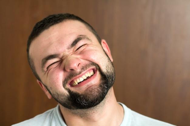 Portret przystojny brodaty czarnowłosy inteligentny nowoczesny młody człowiek w okularach z krótką fryzurą i miłymi czarnymi oczami uśmiechający się na niewyraźne tło. koncepcja młodości i zaufania.