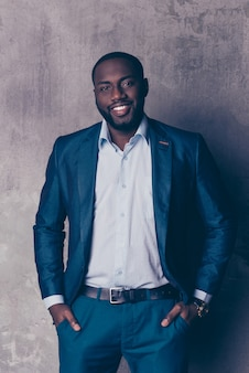 Portret przystojny brodaty mężczyzna afroamerican w formalnej odzieży, trzymając się za ręce w kieszeniach