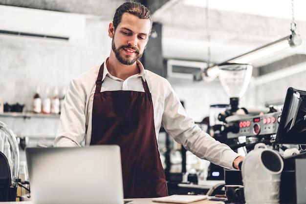 Portret przystojny brodaty mężczyzna barista właściciel małej firmy pracującej z laptopem za barem licznika w kawiarni