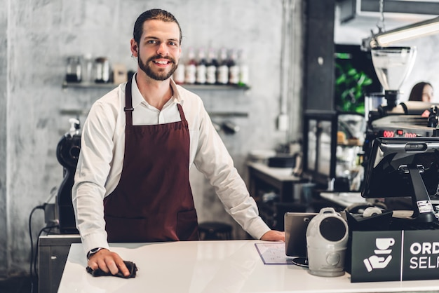 Portret przystojny brodaty mężczyzna barista właściciel małej firmy pracujący za barem licznika w kawiarni