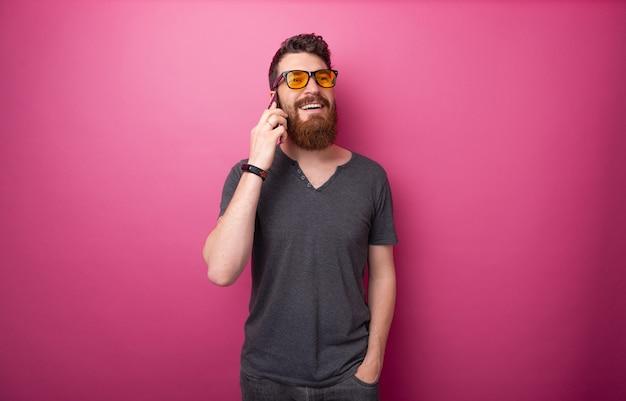 Portret przystojny brodaty mężczyzna rozmawia przez telefon z przyjaciółmi na na białym tle różowym