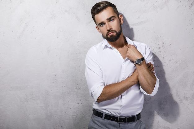 Portret przystojny brodaty mężczyzna ubrany w białą koszulę pozuje przed betonową ścianą