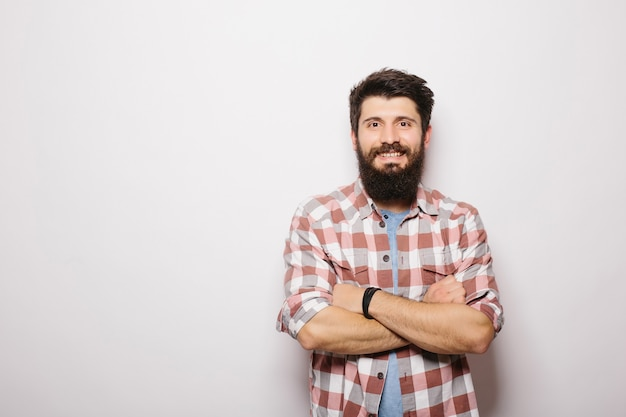 Portret przystojny brodaty mężczyzna uśmiecha się, na białym tle nad białą ścianą