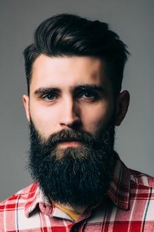 Portret przystojny brodaty młody człowiek na białym tle na szarej ścianie