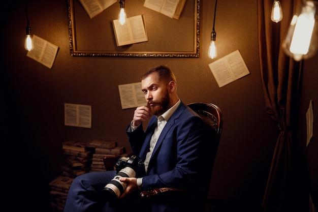 Portret przystojny brodaty młody człowiek ubrany w niebieski garnitur, biała koszula siedzi w luksusowym bibliotece trzymać aparat. fotograf, kamerzysta.