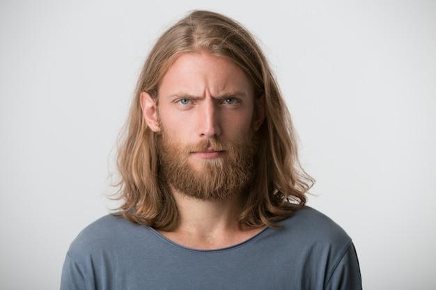 Portret przystojny brodaty młody mężczyzna z blond długimi włosami nosi szarą koszulkę wygląda poważnie i pewnie na białym tle na białej ścianie