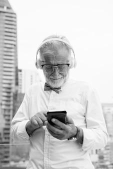 Portret przystojny brodaty starszy turysta na sobie stylowe ubrania podczas zwiedzania bangkoku w czerni i bieli