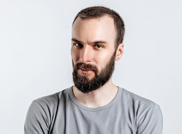 Portret przystojny brutalny poważny mężczyzna brunetka na białej ścianie ze skrzyżowanymi rękami