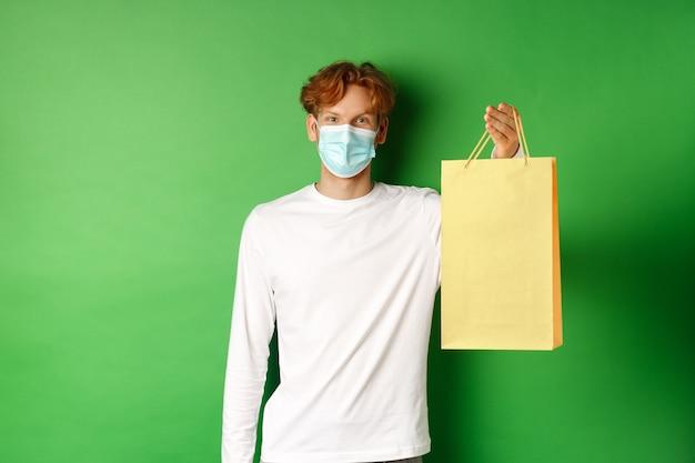 Portret przystojny chłopak w masce twarzy, dając torbę na zakupy z prezentem walentynki, uśmiechając się z oczami, stojąc na zielonym tle.