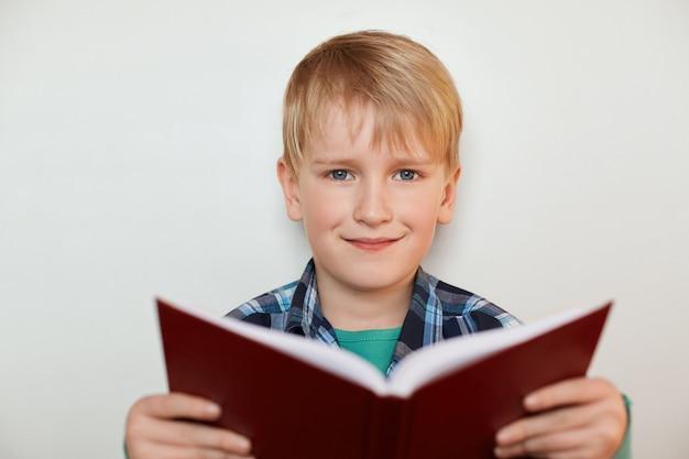 Portret przystojny chłopczyk o jasnych włosach i niebieskich oczach, trzymając książkę w dłoniach, stojąc nad białym