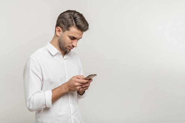 Portret przystojny ciekawy facet ubrany dorywczo wysyłanie i otrzymywanie wiadomości na białym tle nad białym