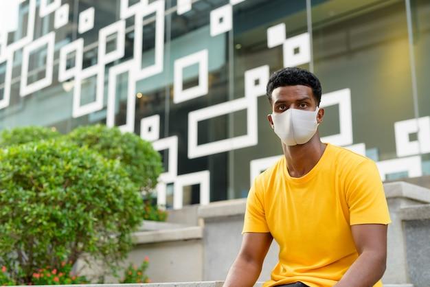 Portret przystojny czarny afrykański mężczyzna ubrany w żółty t-shirt na zewnątrz w mieście w bangkoku, tajlandia