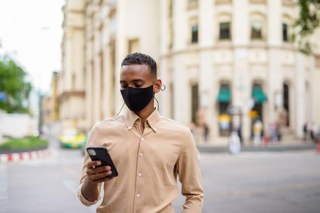 Portret przystojny czarny młody biznesmen afryki na sobie ubranie na zewnątrz w mieście i przy użyciu telefonu komórkowego