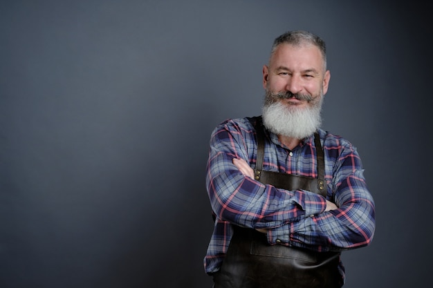 Portret przystojny dojrzały brodaty mężczyzna ubrany skórzany fartuch na białym tle na szarej ścianie, kaukaski robotnik z brodą uśmiechnięty