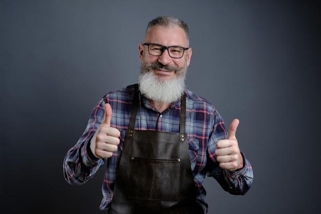 Portret przystojny dojrzały brodaty mężczyzna ubrany w skórzany fartuch, wskazując kciuki do góry na szarej ścianie kaukaski robotnik z brodą uśmiechnięty