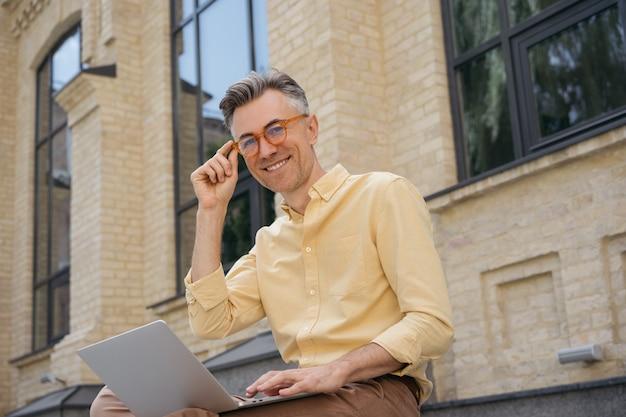 Portret przystojny dojrzały mężczyzna pracujący projekt, siedząc na zewnątrz. pomyślna koncepcja biznesowa