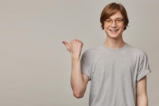 Portret przystojny, dorosły mężczyzna o blond włosach. nosi szary t-shirt, okulary i ma szelki. wskazując kciukiem w lewo na miejsce na kopię, odizolowane na szarej ścianie
