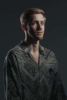 Portret przystojny facet kaukaski w koszuli boho na czarno.