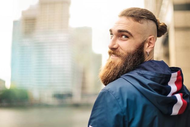 Portret przystojny facet spaceru na ulicy i uśmiechnięty