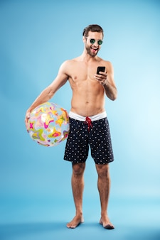 Portret przystojny facet trzyma plażową piłkę
