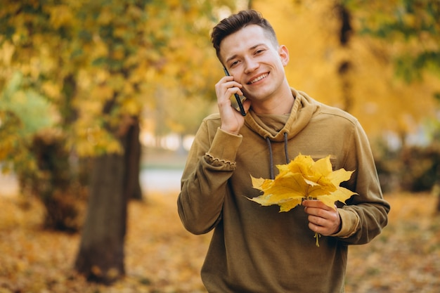 Portret przystojny i szczęśliwy facet uśmiecha się i rozmawia przez telefon w jesiennym parku