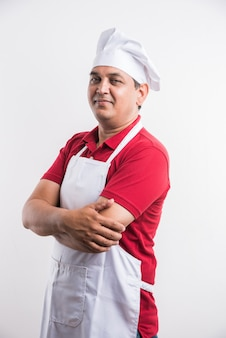 Portret przystojny indyjski mężczyzna kucharz pozuje podczas wykonywania czynności