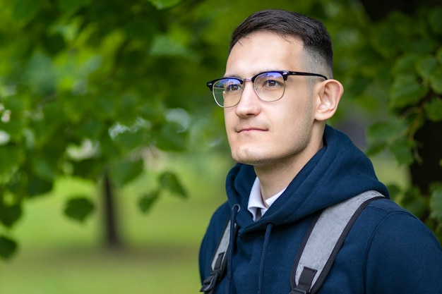 Portret przystojny inteligentny student college'u na zewnątrz w zielonym parku