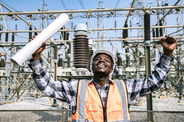 Portret przystojny inżynier posiadający papierowy plan sprawdzania miejsca pracy na miejscu i nosić kask przed elektrownią dużej mocy. widok wykonawcy z tyłu na tle nowoczesnego budynku energetycznego.
