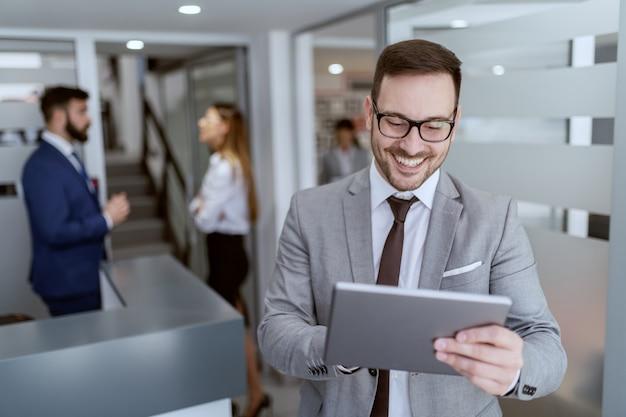 Portret przystojny kaukaski uśmiechnięty biznesmen nieogolony w garniturze i okularach stojący w hali i za pomocą tabletu.