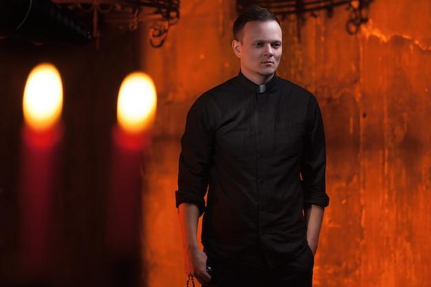 Portret przystojny ksiądz katolicki lub pastor z obrożą, ciemnoczerwone tło.