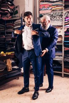 Portret przystojny męski klient próbuje żakiet w sklepie