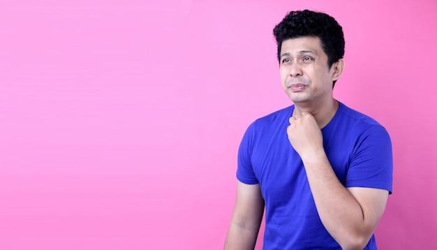 Portret przystojny mężczyzna azji na bólach gardła na różowym tle w studio