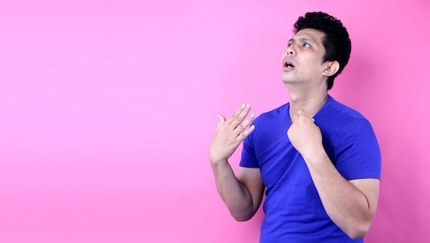 Portret przystojny mężczyzna azji poczuj gorącą pogodę na różowym tle w studio