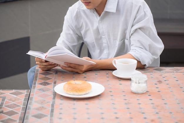 Portret przystojny mężczyzna, czytając książkę i ciesząc się jego kawą.