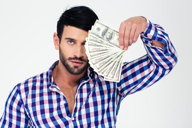Portret przystojny mężczyzna dorywczo gospodarstwa rachunki dolara na białym tle na białej ścianie