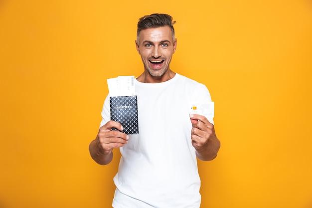 Portret przystojny mężczyzna emocjonalny pozuje na białym tle na żółtej ścianie, trzymając paszport z biletami i kartą kredytową.