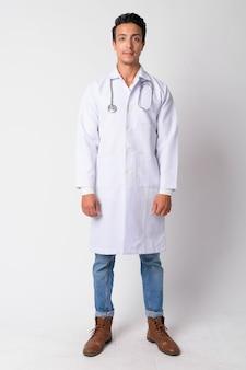 Portret przystojny mężczyzna hispanic lekarza przeciw białej ścianie