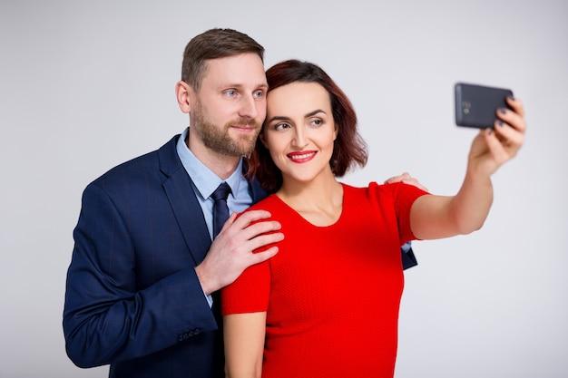 Portret przystojny mężczyzna i piękna kobieta robi zdjęcie selfie ze smartfonem na białym tle