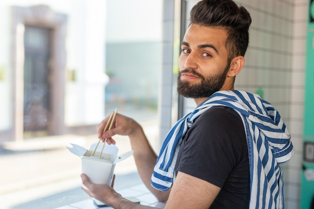 Portret przystojny mężczyzna, jedzenie makaron chiński w kawiarni i patrząc przez okno. pojęcie zdrowej kuchni azjatyckiej.
