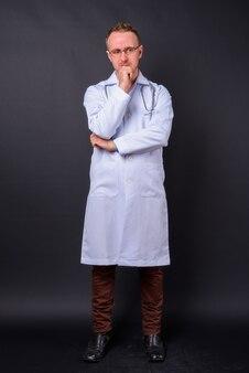 Portret przystojny mężczyzna lekarz z blond włosami na czarnej ścianie