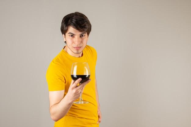 Portret przystojny mężczyzna modelu w żółtej koszuli trzyma kieliszek wina.