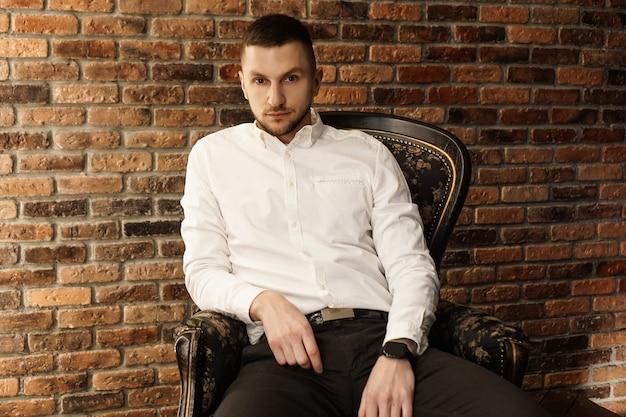 Portret przystojny mężczyzna modny w białej koszuli siedzi na krześle w loft studio fotograficznym. młody biznesmen
