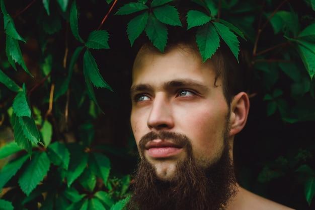 Portret przystojny mężczyzna na zielone letnie liście. moda brunetka mężczyzna z niebieskimi oczami, portret w dzikich liściach (winogrona), naturalne tło.